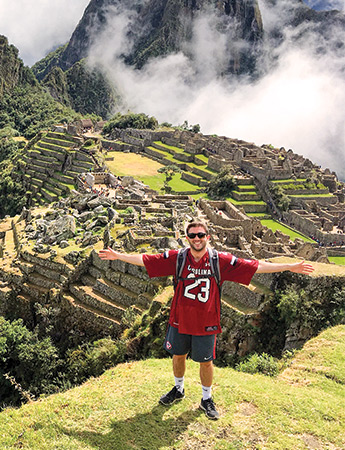 Student wearing a garnet football jersey standing with his arms stretched out in front of Machu Picchu.