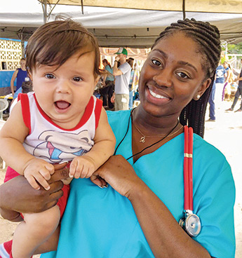Shir'Mel McCullough wearing blue scrubs and a red stethoscope while holding a baby and smiling at the camera.