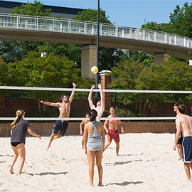 Group of students playing sand volleyball