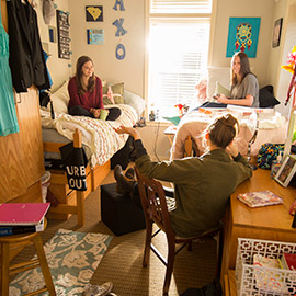 Three students talking in residential hall room