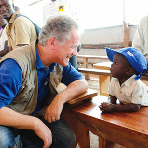 david beasley kneels and smiles at a child in a blue ball cap